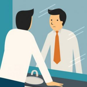 businessman looking at himself in the mirror