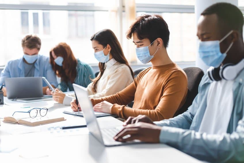 Teamwork in corporate company and returning to work after quarantine covid-19. Focused millennial people wearing medical masks working using laptop and tablet, writing at workplace in office interior